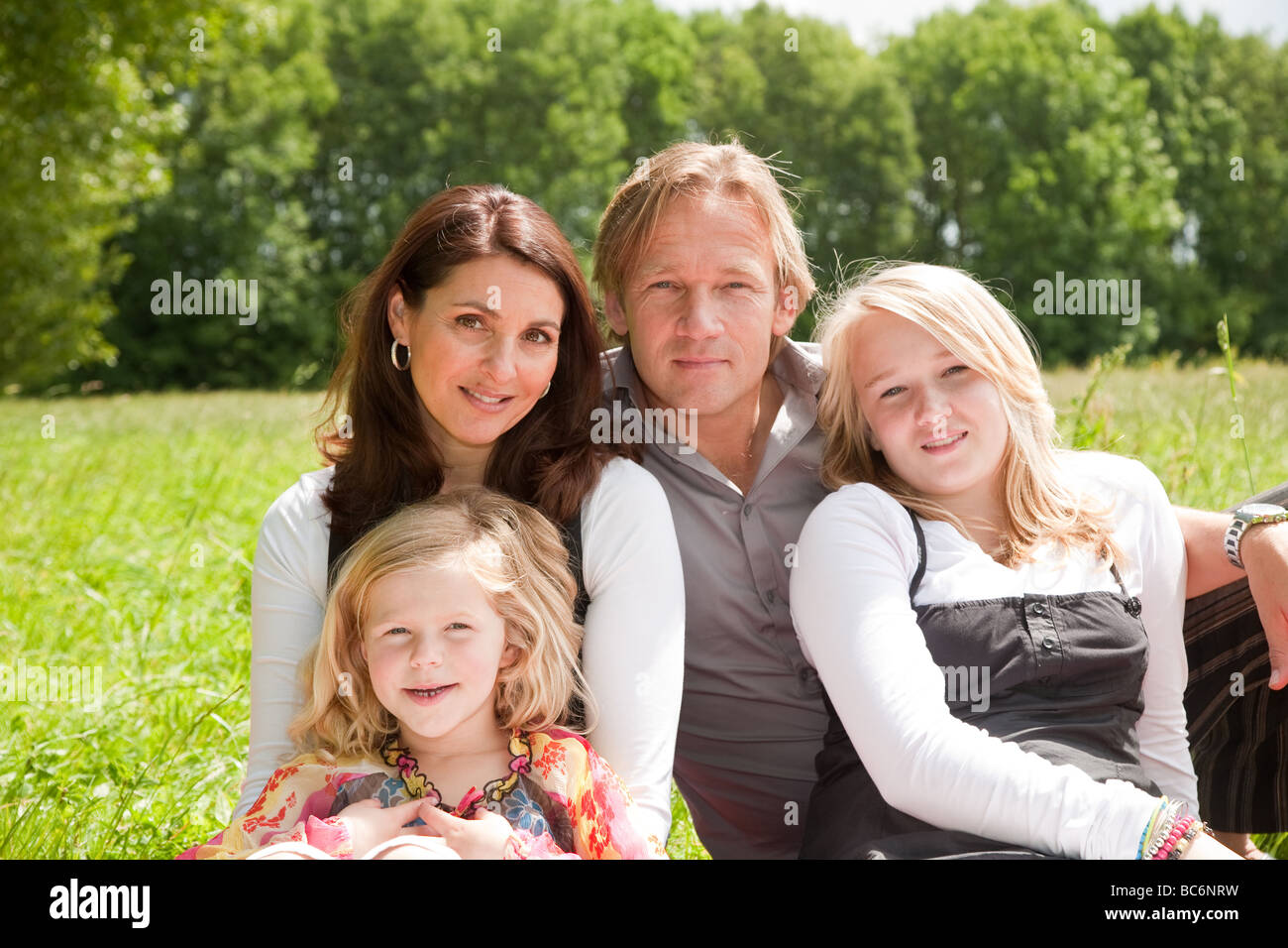 Beautiful young family outdoors in the field - Stock Image