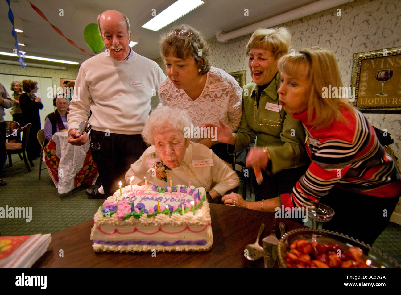 Assisted By Family And Friends A Centenarian Blows Out The Candles On Her Cake During
