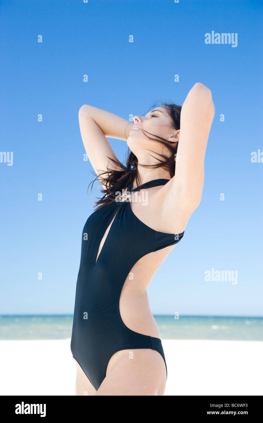 woman on beach in black swimming suit - Stock Image