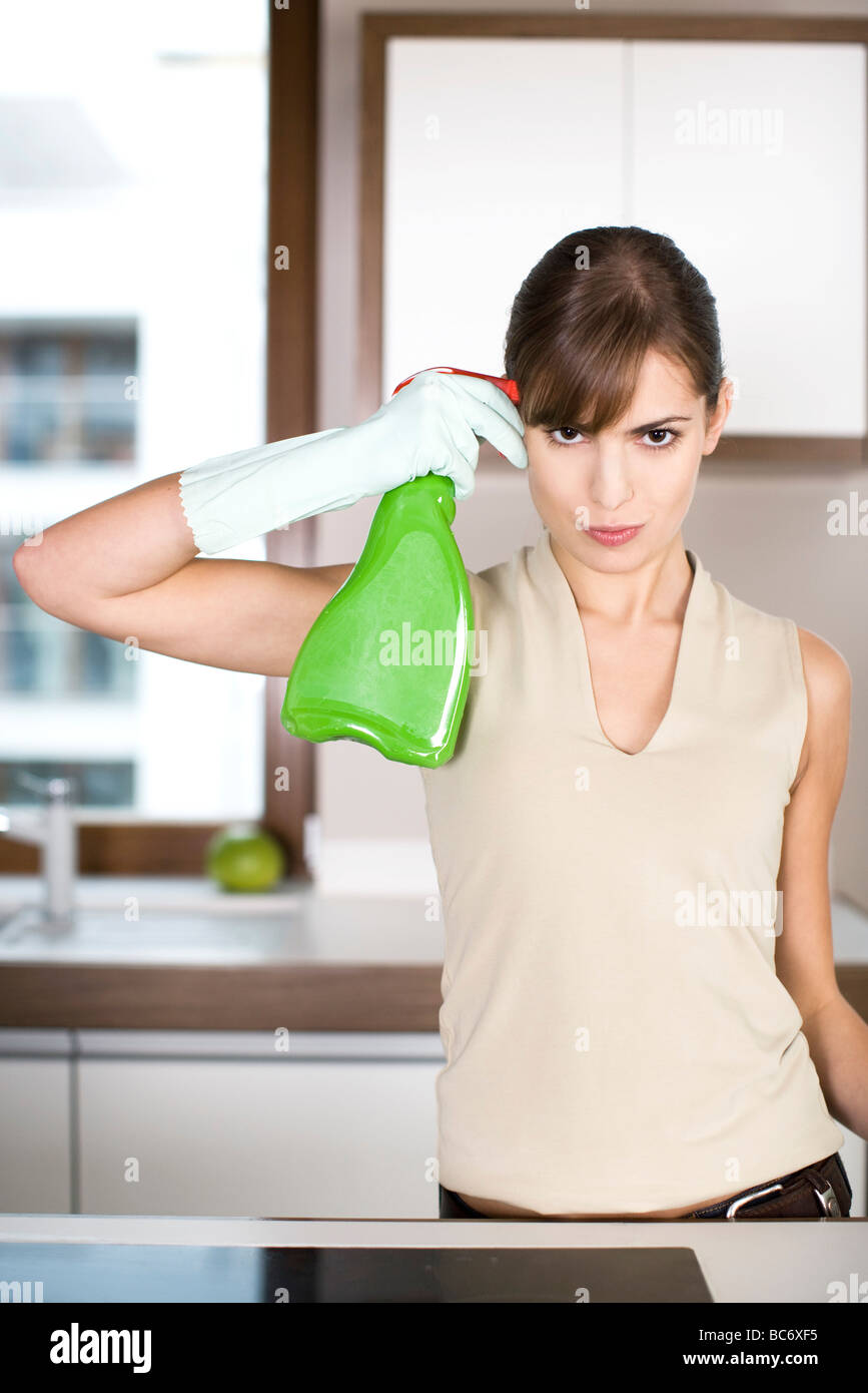 woman pointing spray at her head - Stock Image