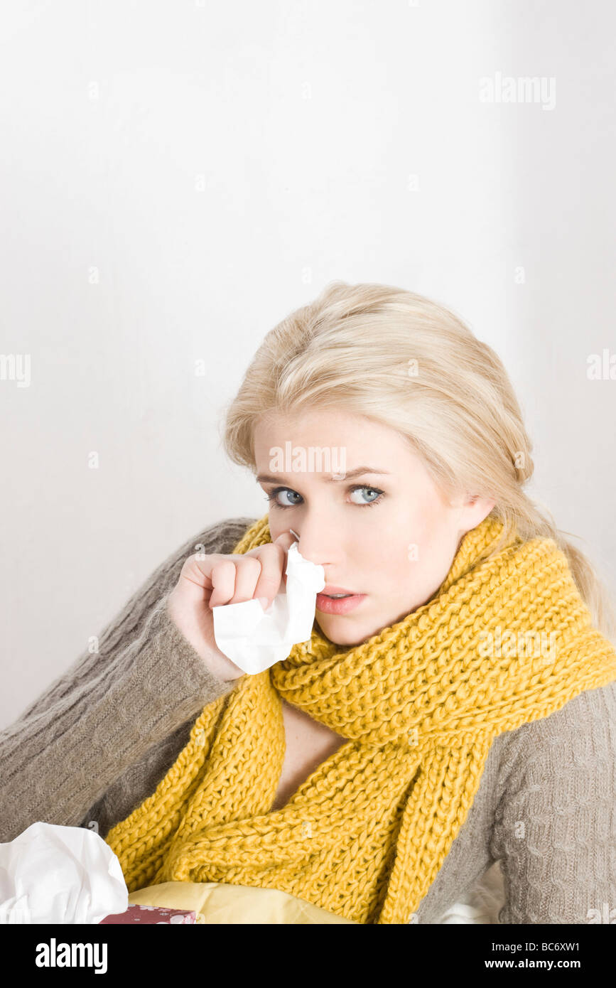 sick woman with tissue - Stock Image