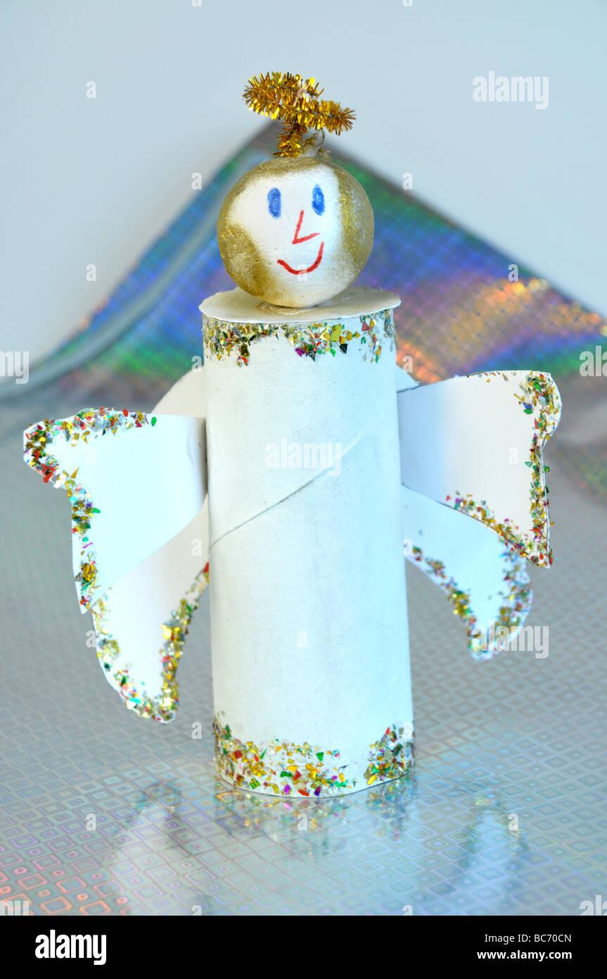 handmade angel standing on Christmas paper. - Stock Image