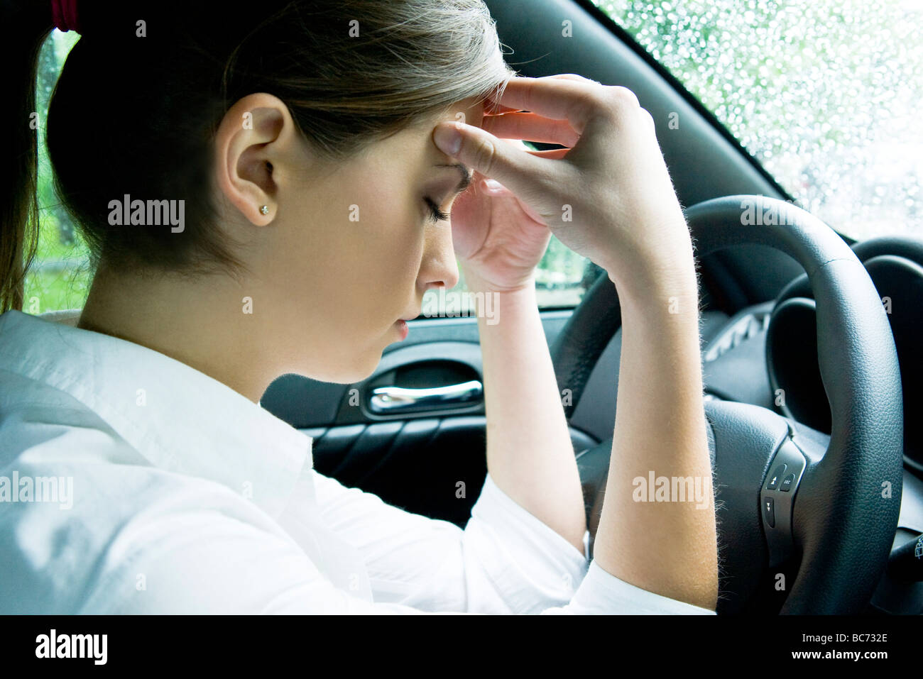woman with headache in the car - Stock Image