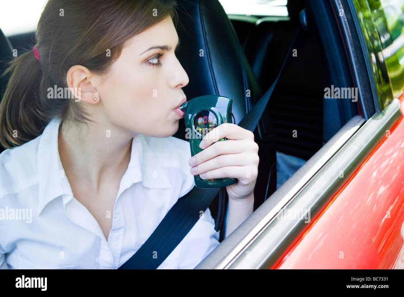 woman breathing into breathalyzer - Stock Image