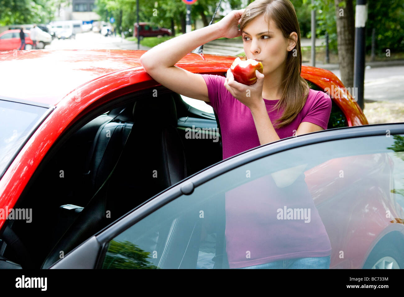 woman eating apple in car - Stock Image