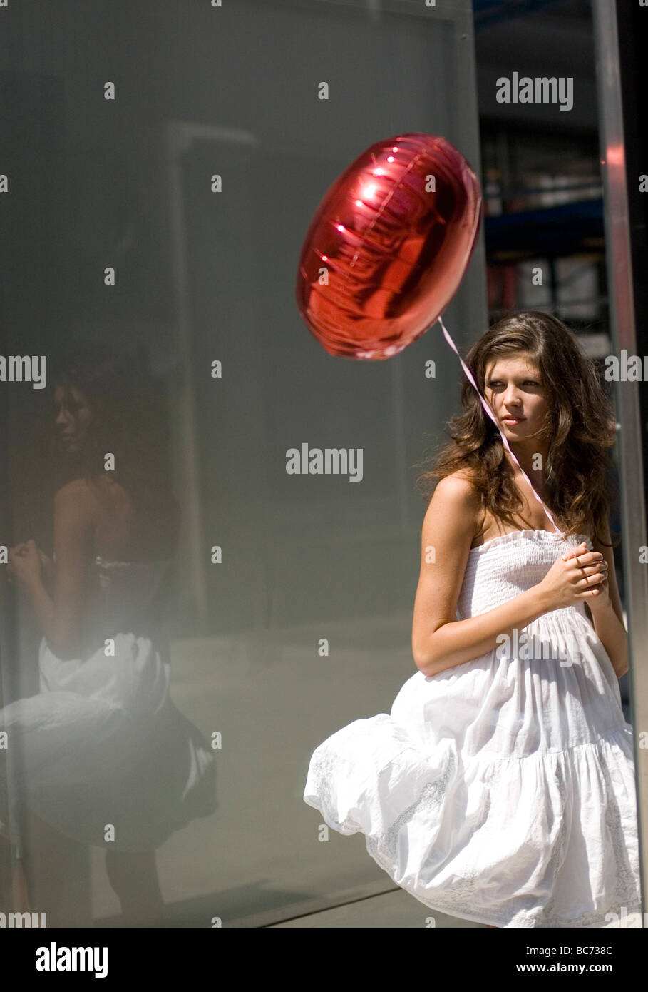 Woman with red balloon in city center - Stock Image