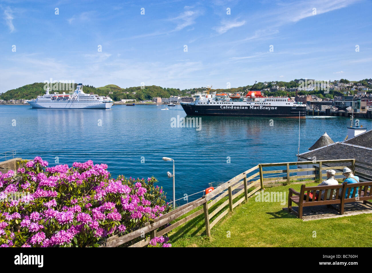 Calmac car ferry Isle of Mull leaving Oban en route to Mull with cruise ship Astor moored in the harbour. - Stock Image