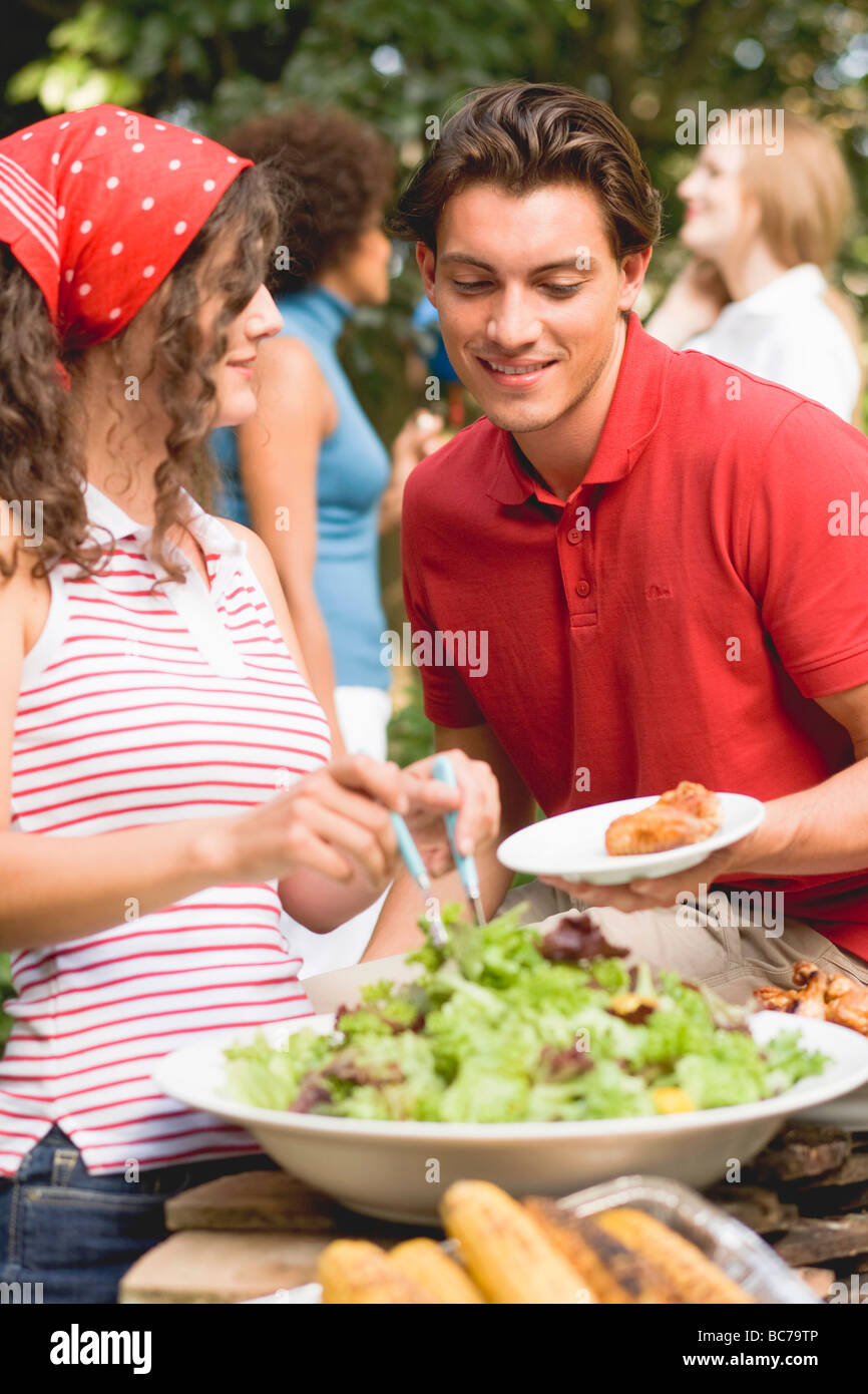 Young woman serving green salad at a barbecue - - Stock Image