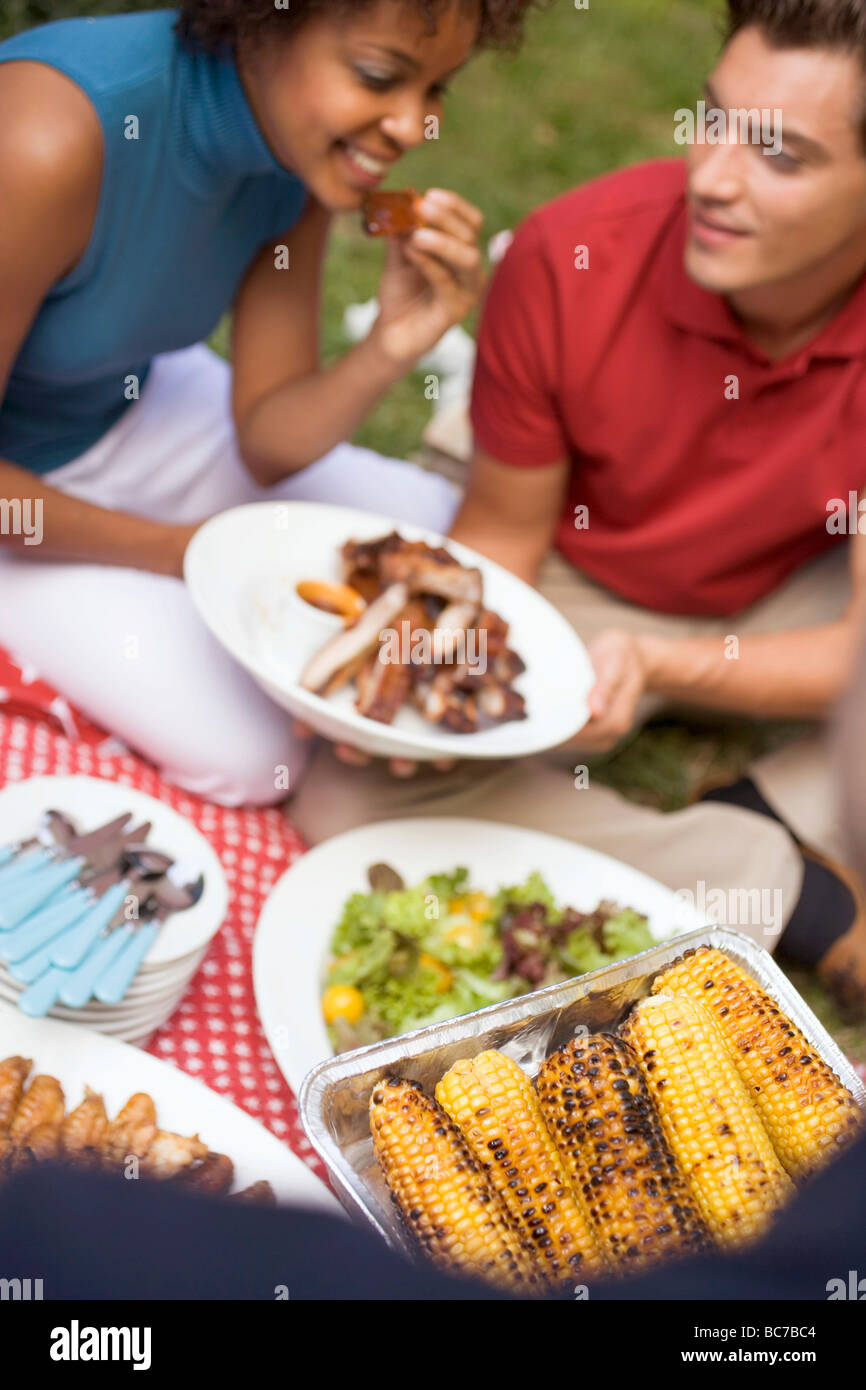 Couple with grilled spare ribs, corn on the cob, salad, on grass - - Stock Image