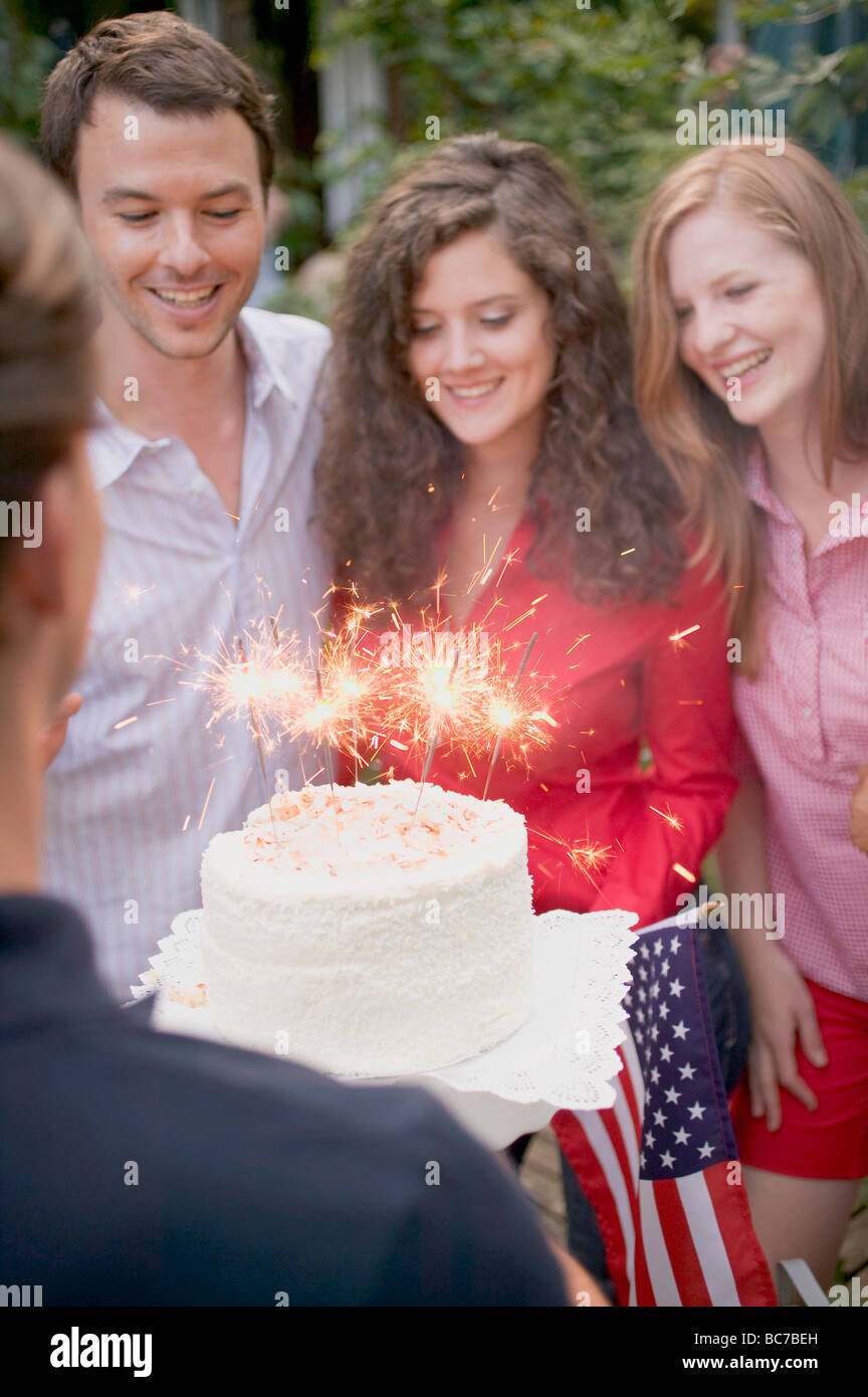 Man serving coconut cake with sparklers (4th of July, USA) - - Stock Image