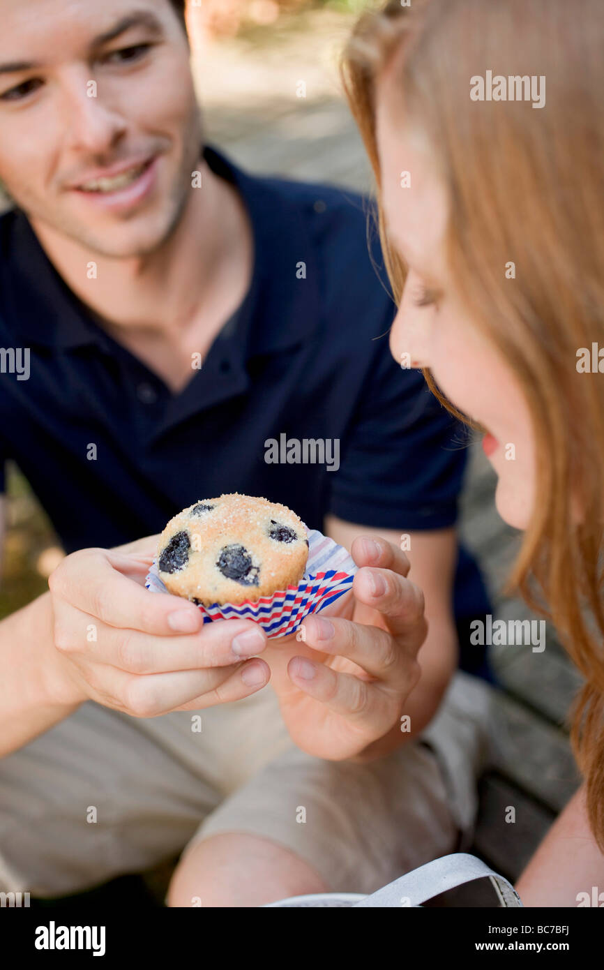Man handing woman a blueberry muffin - - Stock Image