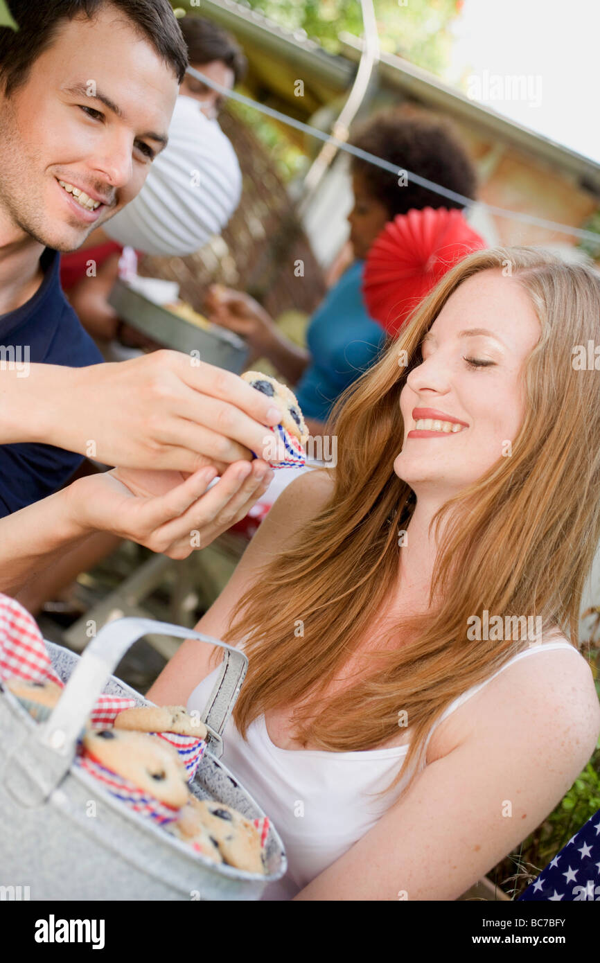 Cheerful couple with blueberry muffins at a garden party - - Stock Image