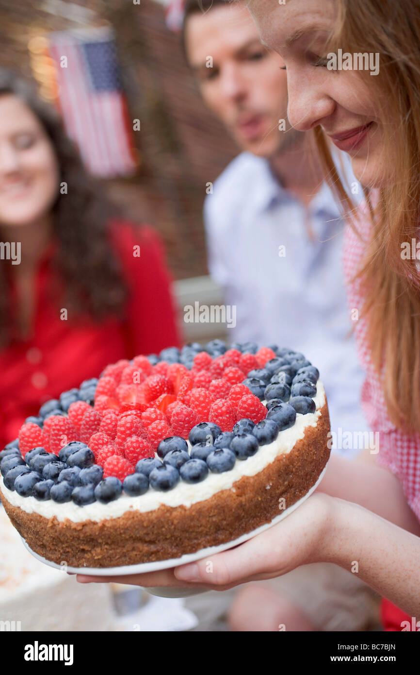 Woman holding a berry cake (4th of July, USA) - - Stock Image