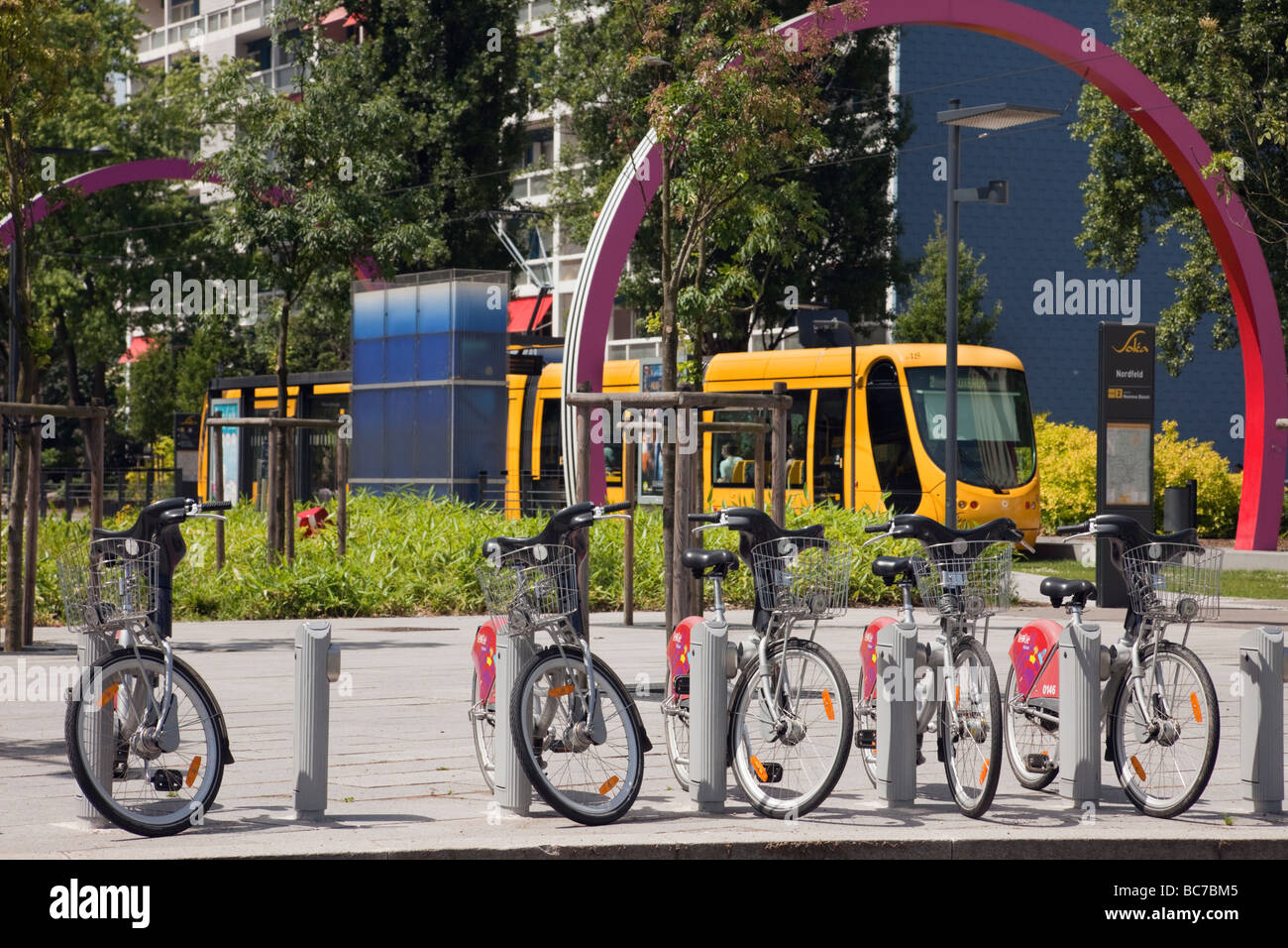 Mulhouse Alsace France Europe Velocity electric bikes for rent by tramway station with yellow tram train on light - Stock Image