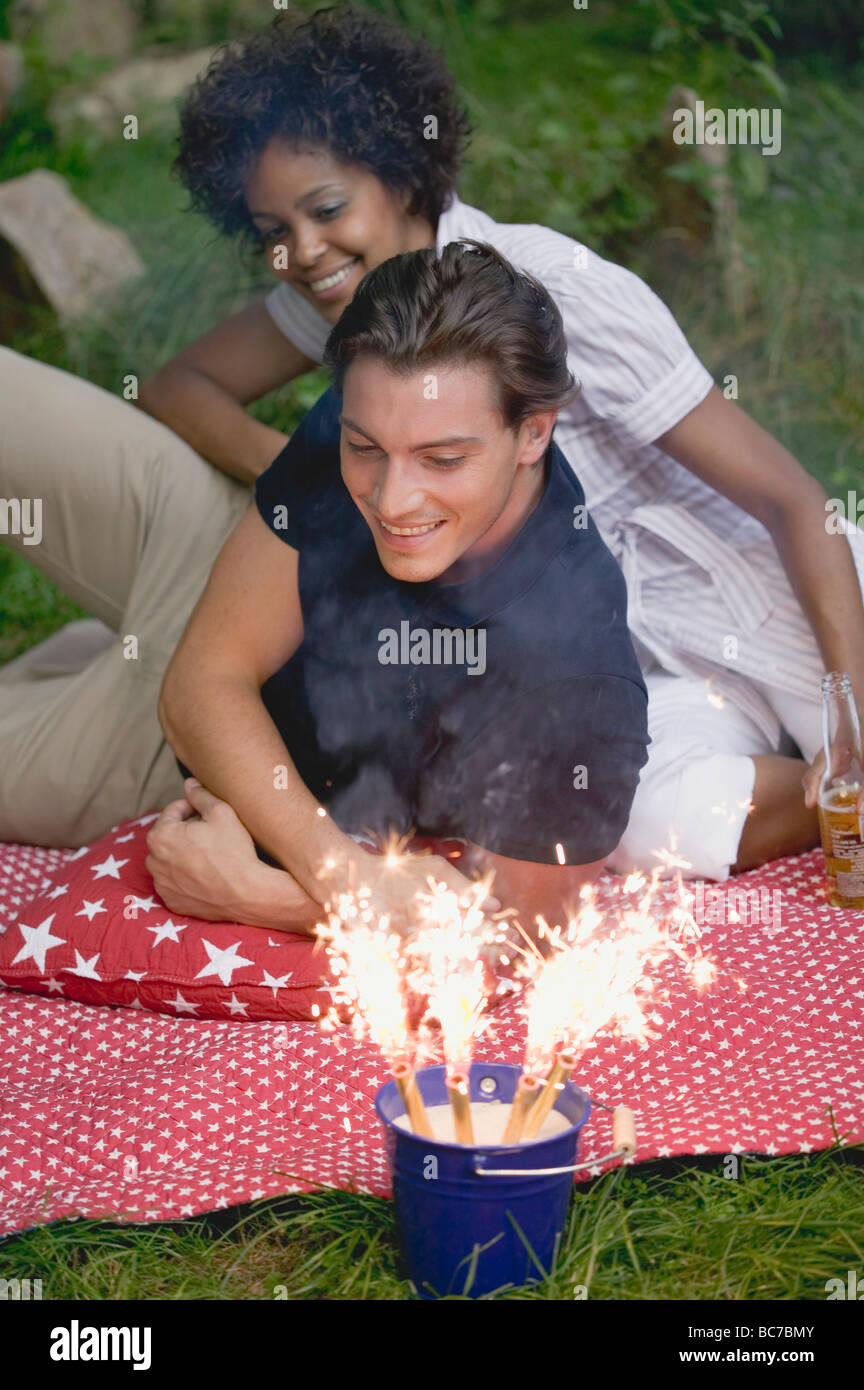 Couple with sparklers at a 4th of July picnic (USA) - - Stock Image
