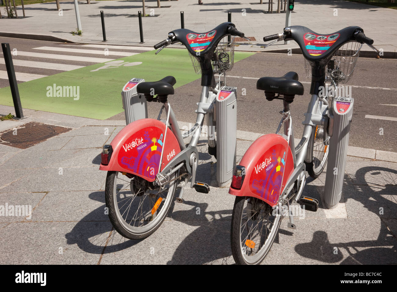 Mulhouse Alsace France Europe Velocity electric bikes for rent by pedestrian and bicycle road crossing in city - Stock Image