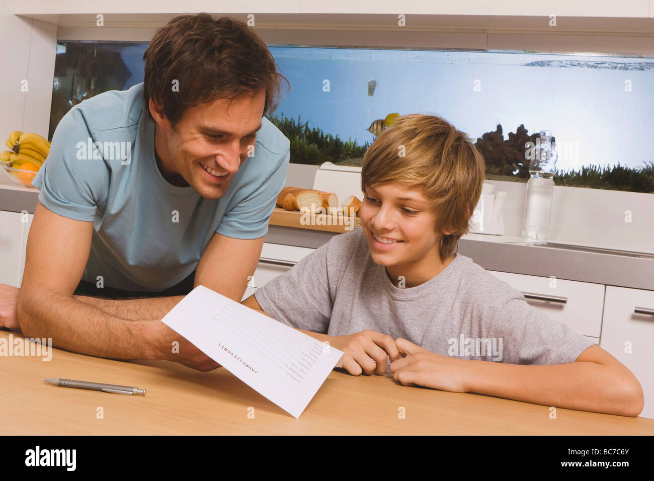 Father and son (13-14) looking at report card - Stock Image