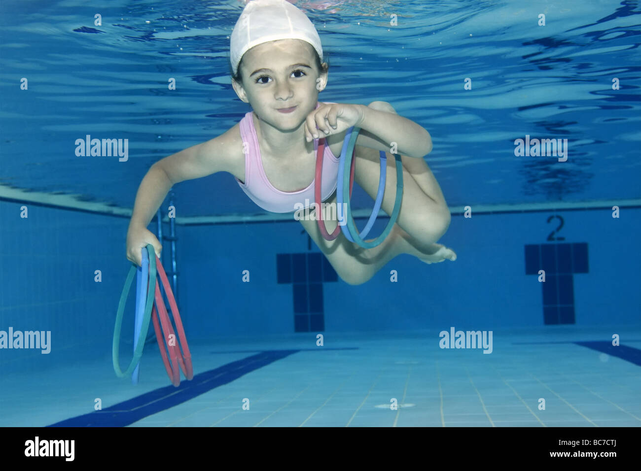 Underwater picture of a girl swimming and playing with toys Stock Photo
