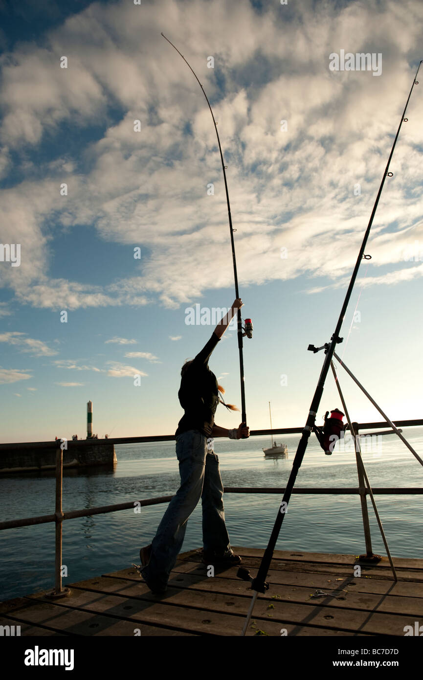 Young woman fishing with rod a line casting off at the jetty at Aberystwyth harbour on a summer evening wales UK Stock Photo