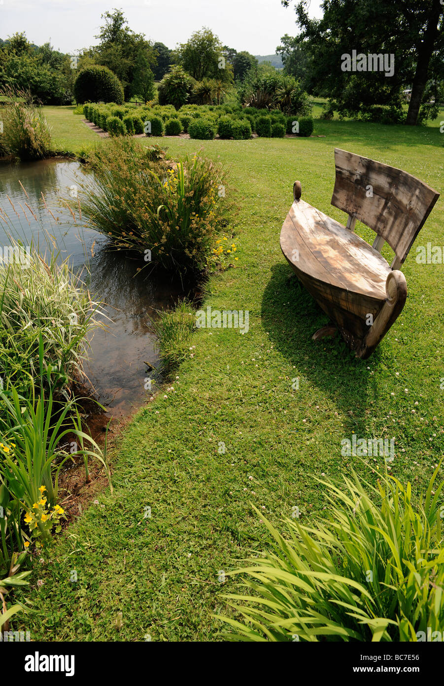 Boat shaped seat by the lake of a landscaped English Garden in Stoberry Park, Somerset, UK Stock Photo
