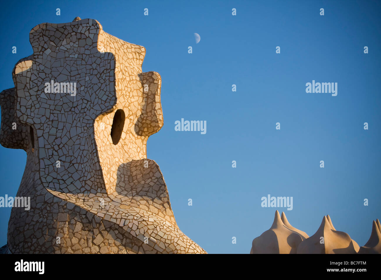 Moon and Chimneys at sunset and blue sky at rooftop of Casa Milà by Gaudi Barcelona Spain - Stock Image