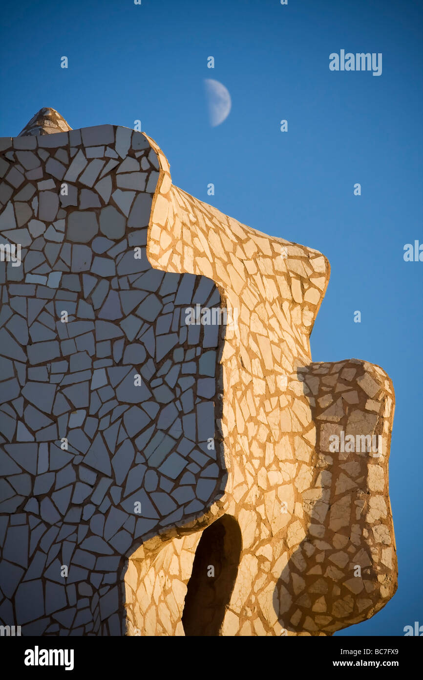 Moon above closeup details of mosaic like chimney sidelighted by sunset at rooftop of Casa Milà Barcelona Spain - Stock Image