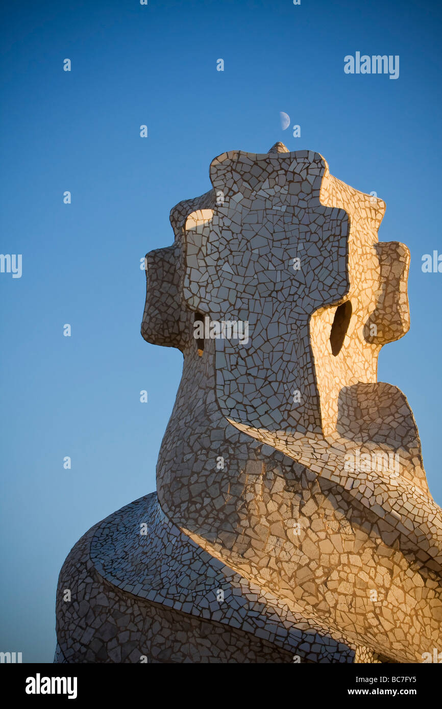 Moon on top of mosaic like chimney side lighted by sunset at rooftop of Casa Milà Barcelona Spain - Stock Image