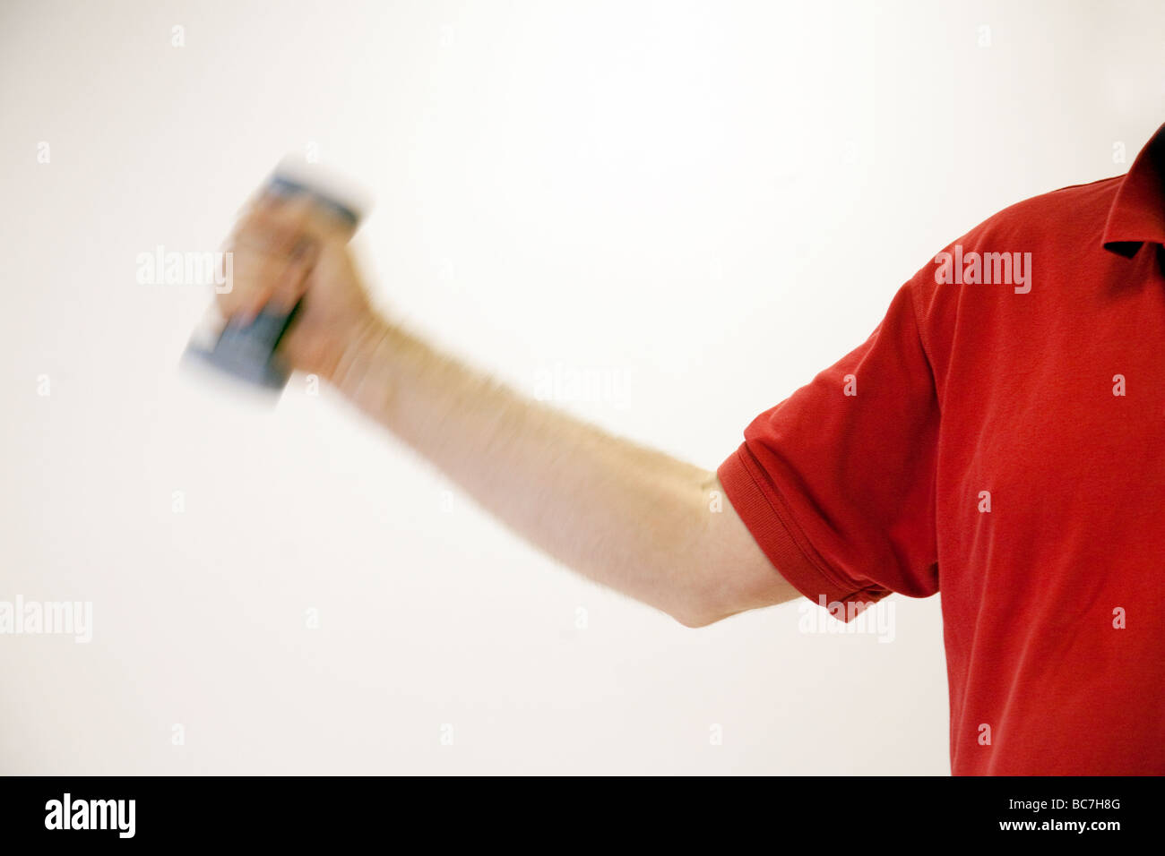 The arm of a middle aged man lifting weights - Stock Image