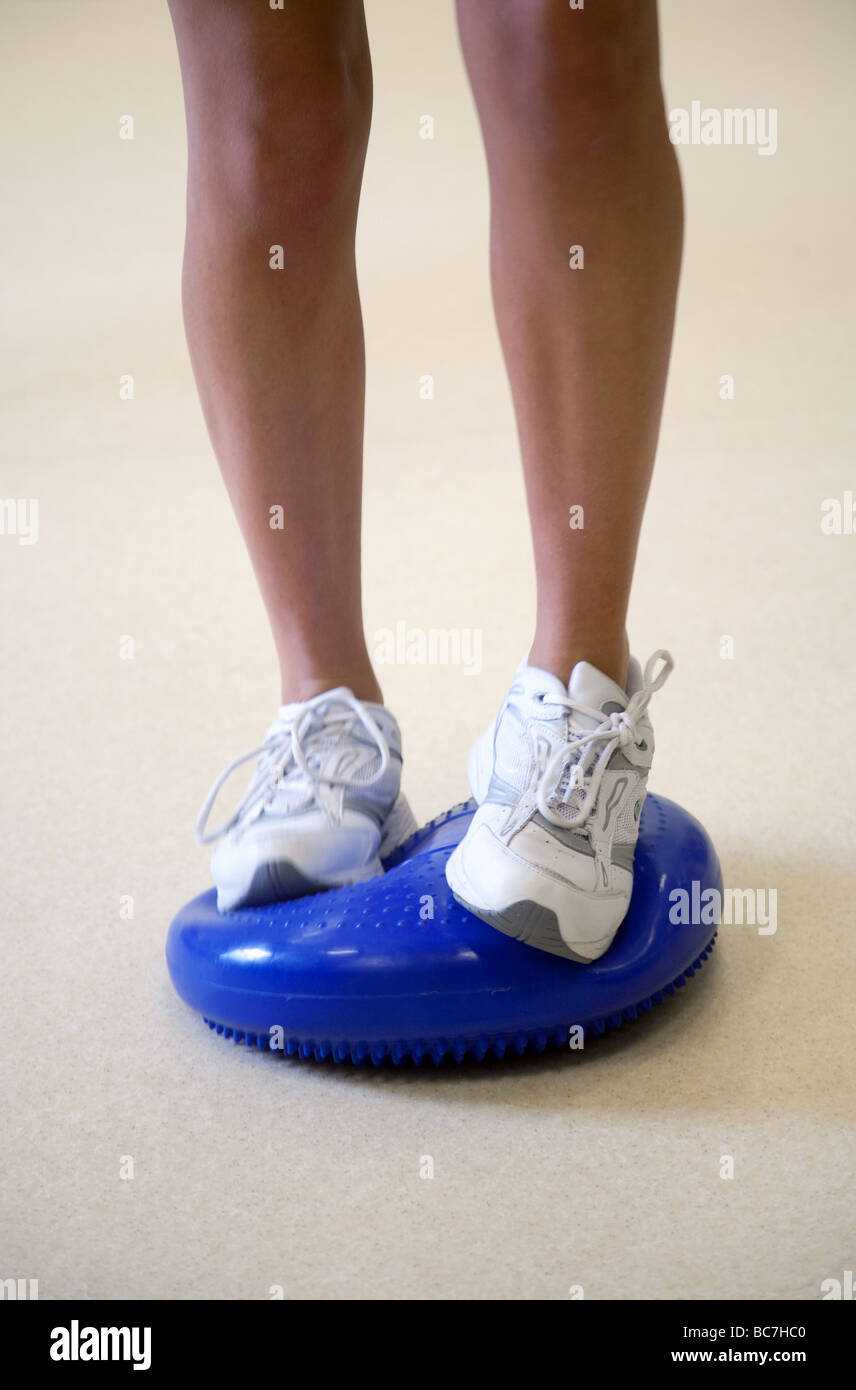 Close up of person exercising on a wobble cushion - Stock Image