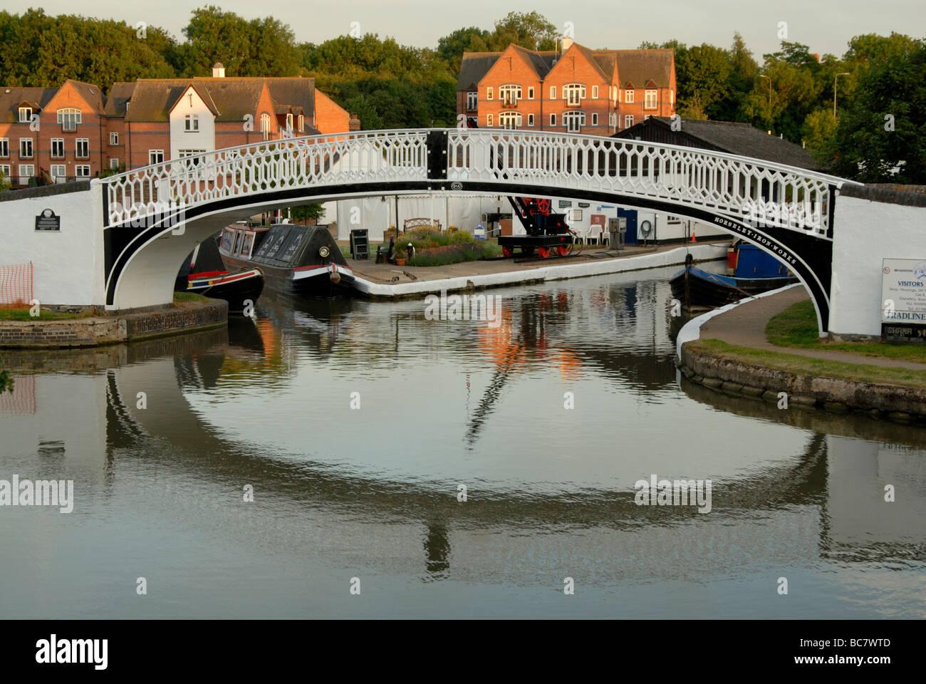 Black and White Victorian ironwork bridge over canal at entrance to Braunston Marina at dusk, Braunston, Northamptonshire - Stock Image