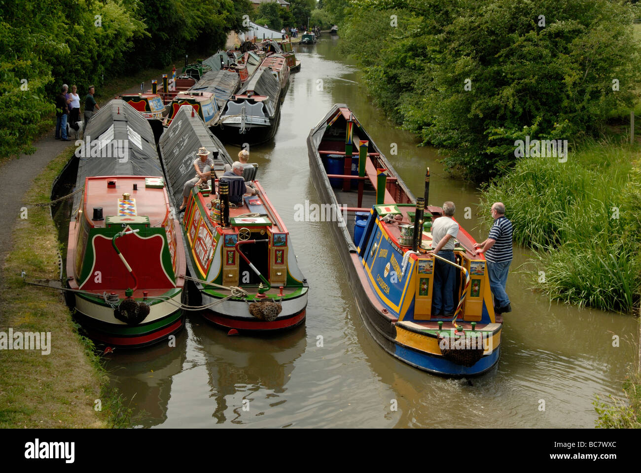 British Waterways working narrowboat passing other working boats under canvas, breasted up on the canal at Braunston, - Stock Image