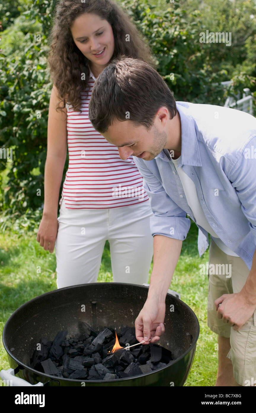 Couple having barbecue in garden (man lighting charcoal) - - Stock Image