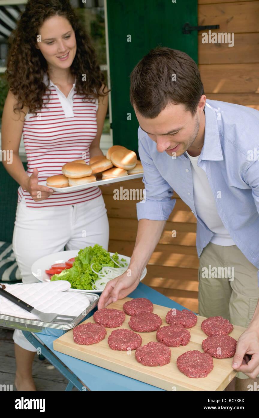Man preparing burgers for grilling, woman bringing buns - - Stock Image
