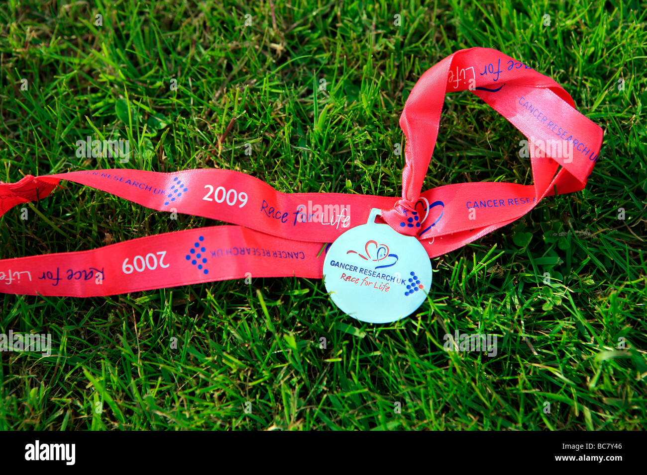 Race for life medal lying on grass - Stock Image