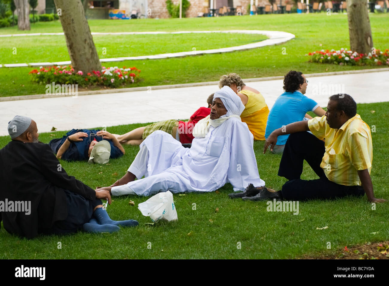 Turkey , Istanbul , Topkapi Palace , tourists & visitors from exotic climes relax in shade on grass lawn in gardens Stock Photo