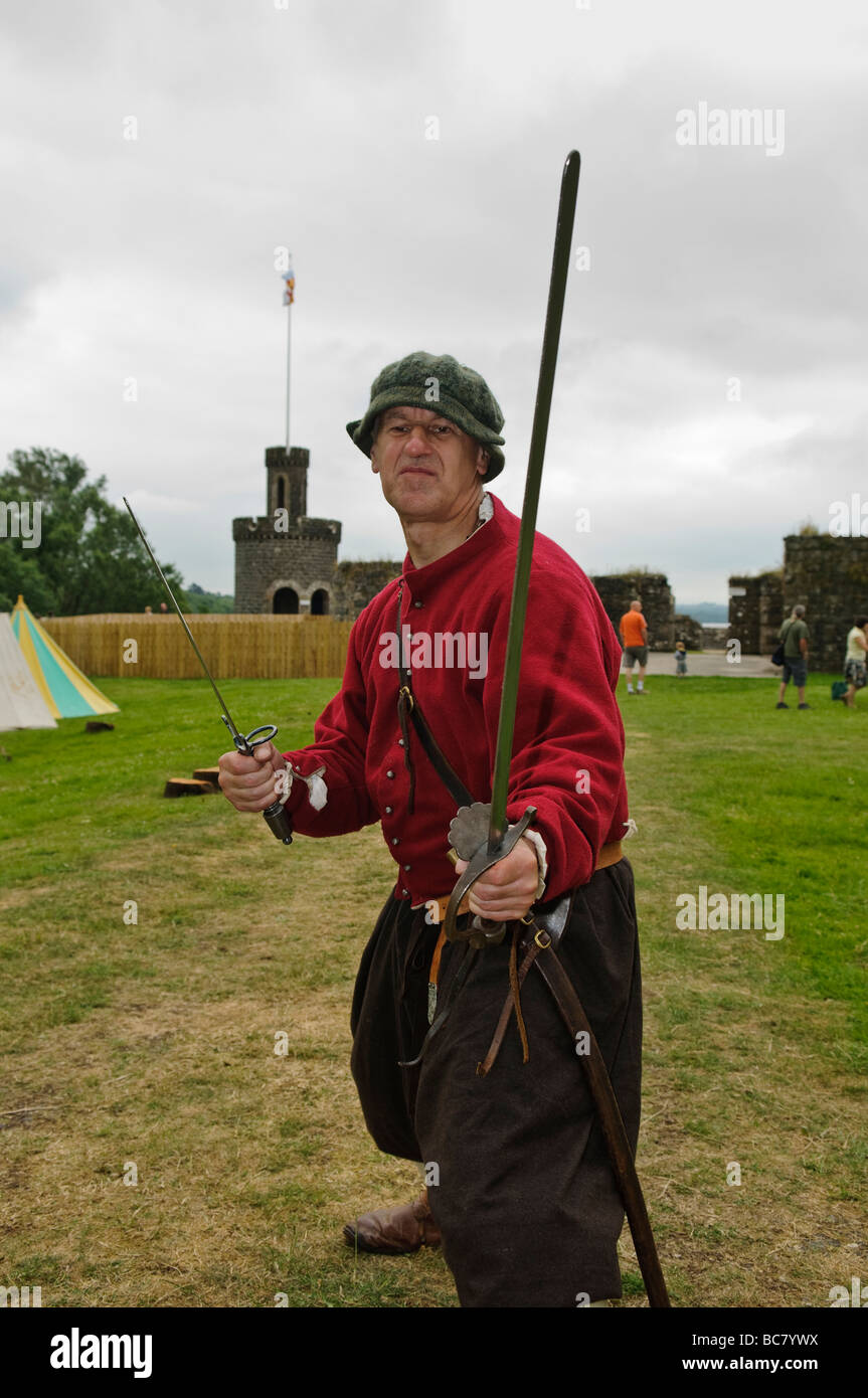 Actor dressed as a medieval foot soldier holds up a sword and dagger ready for combat - Stock Image