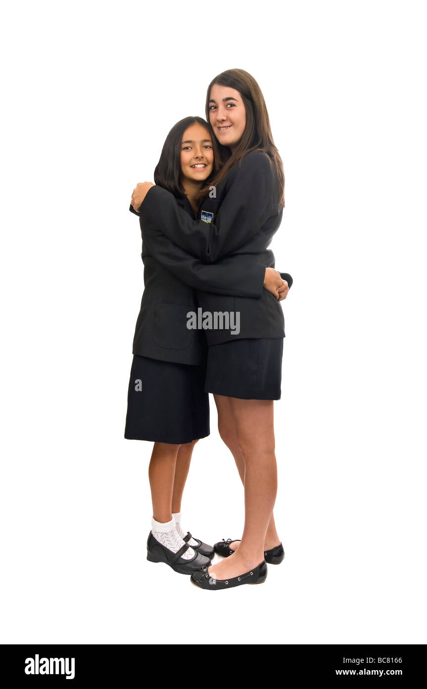 Vertical close up portrait of two teenage sisters in their school uniforms hugging each other against a white background - Stock Image
