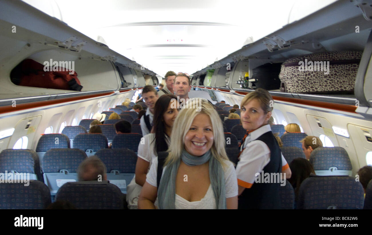 Easyjet passengers finding their seats on a flight - Stock Image