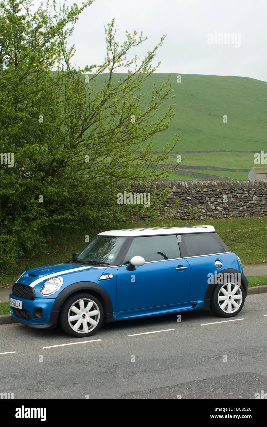 Blue mini cooper s car parked at the side of the road in a village in the English countryside - Stock Image