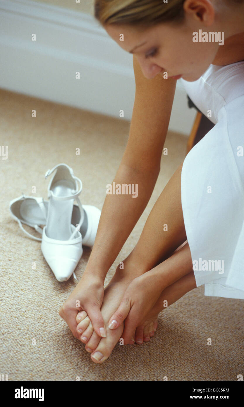 woman massaging her foot as if it is painful after wearing high heels - Stock Image