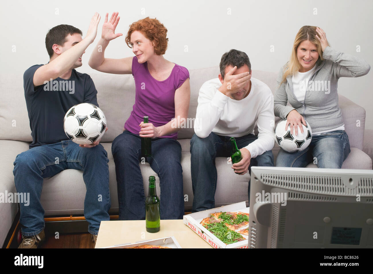 Friends in front of TV with footballs, beer and pizza - - Stock Image