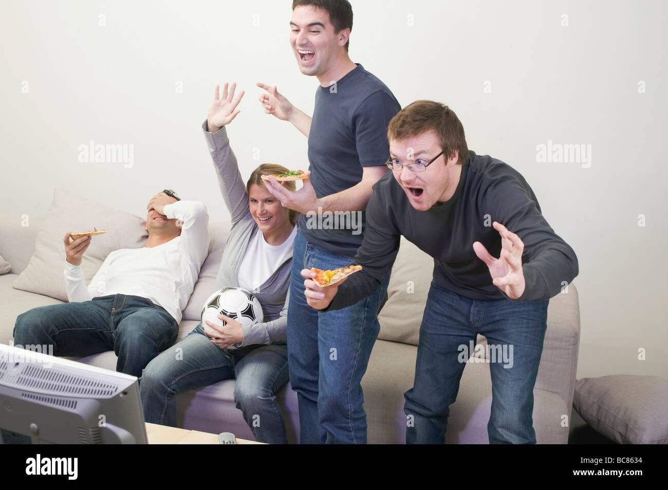 Cheering friends in front of TV with pizza and football - - Stock Image