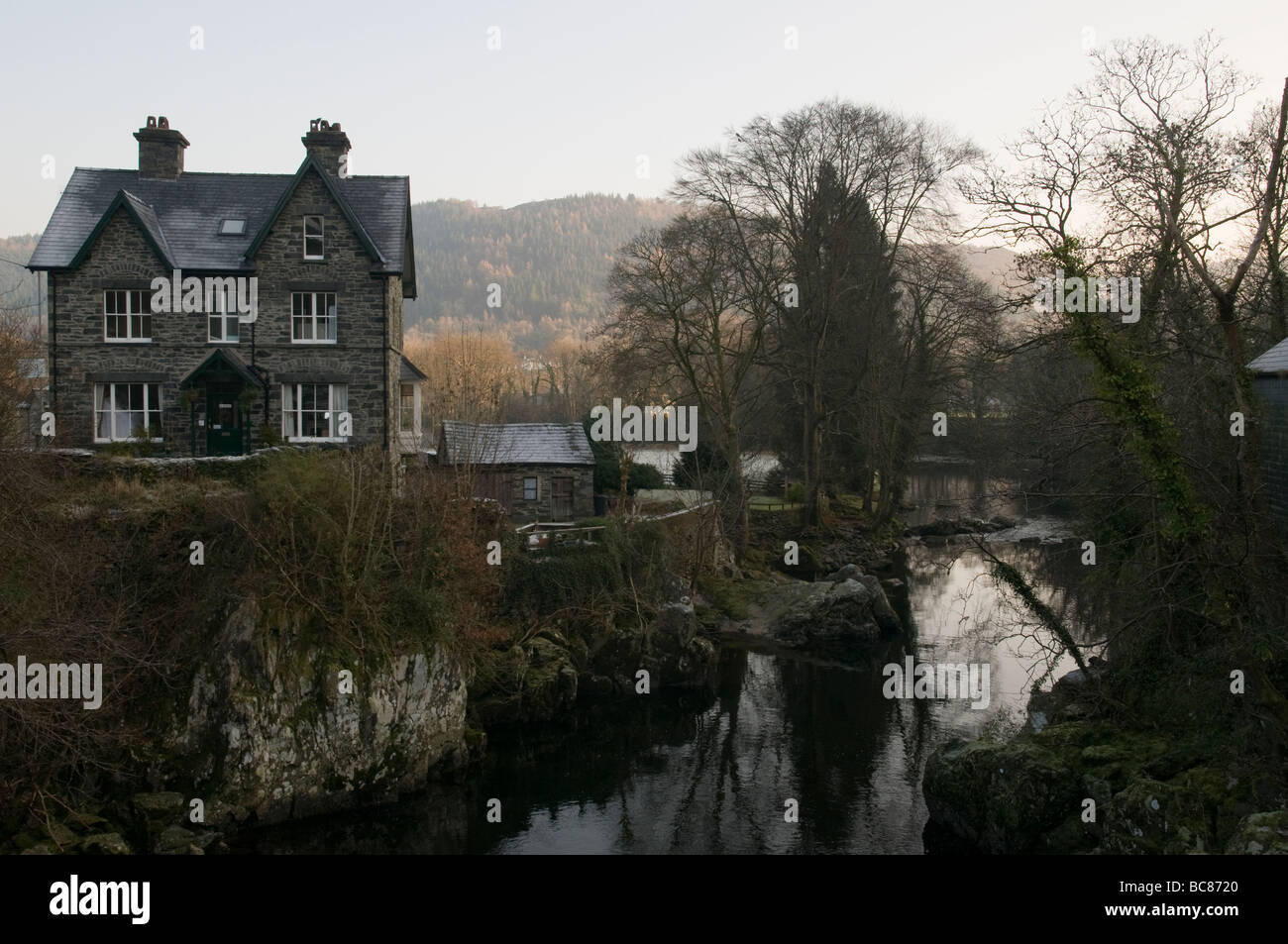 An unlit house by a river in Wales. - Stock Image