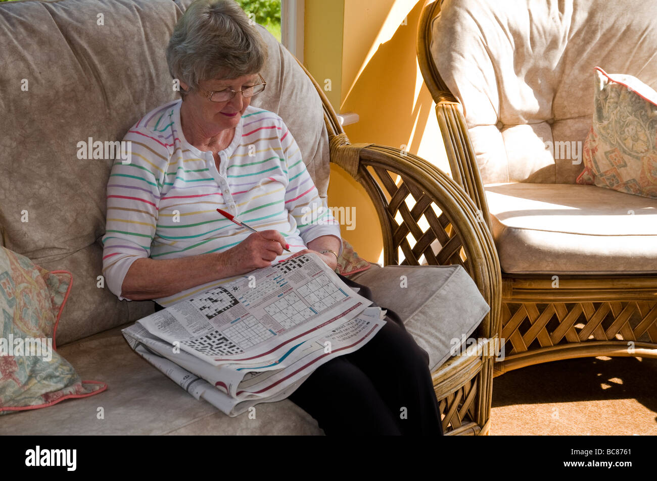 A woman solving puzzles in a daily paper. - Stock Image