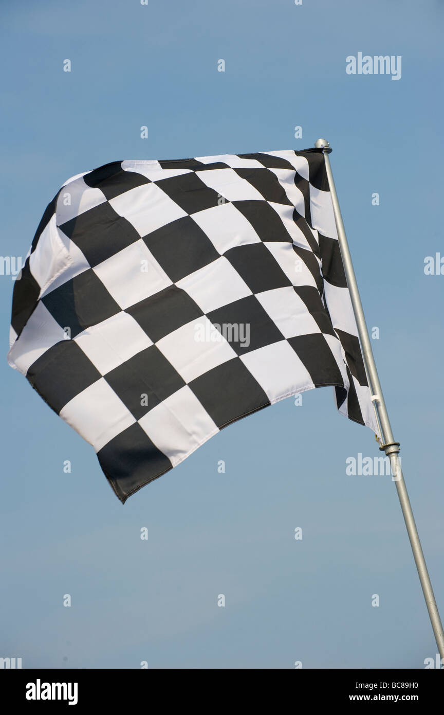 Black and white chequered flag flying on an English beach indicating no swimming in the area - Stock Image
