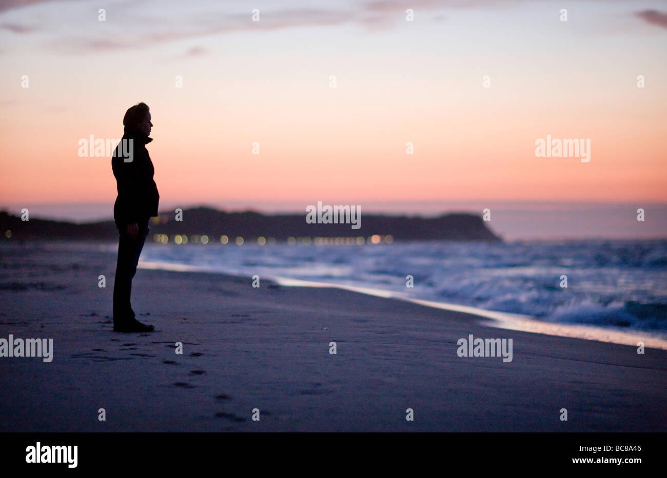 Junge Frau im Sonnenuntergang am Strand von Goehren auf der Insel Ruegen - Stock Image