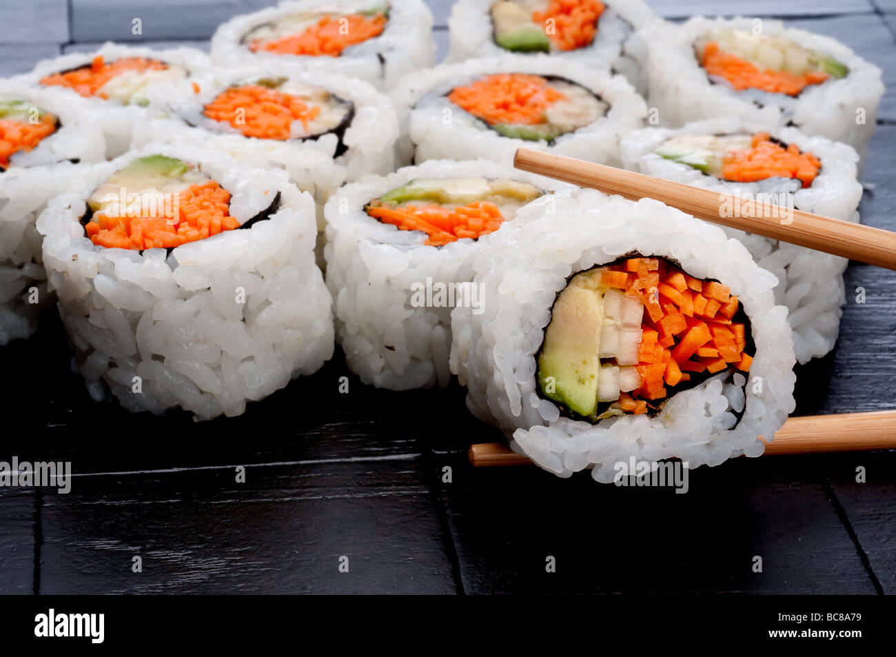 chopsticks holding sushi infront of more sushi on a black textured background - Stock Image