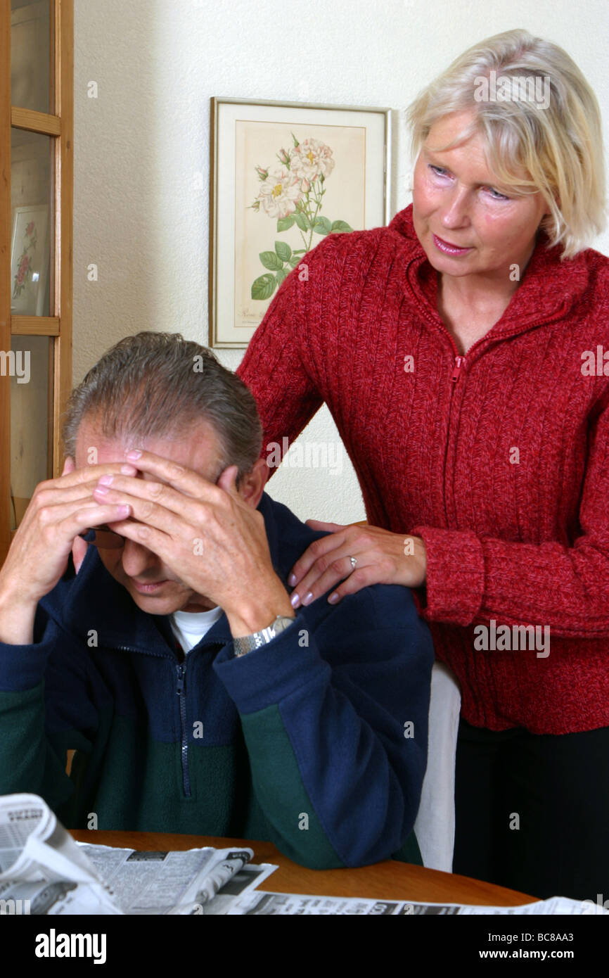 Depressed man comforted by his strong wife, man despondent - Stock Image