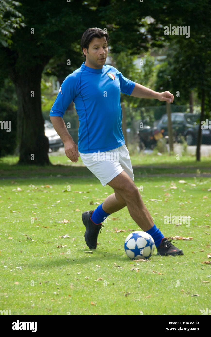 footballer in the park dribbling a ball - Stock Image