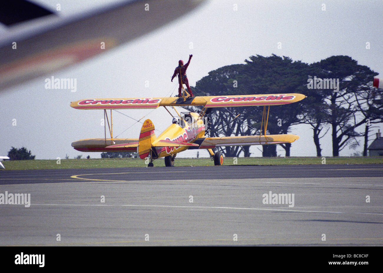 wingwalker on top of yellow Biplane about to take off on runway at airport - Stock Image